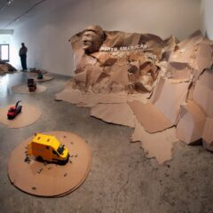 Guggenheim Globetrotters Convoy passes Mount Nicaragua On The Shady side of Mount Rushmore // Cardboard, wood, and acrylic paint // 83 x 190 x 84 inches // 2011
