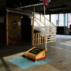 George Walker Bush's Modest Monument // Wood, Screws, Acrylic Paint, Digital Print, Trolley, Wheels , Plastic Pipe, Plastic , Robe, Nickel // 400 x 200 250 cm // 2010