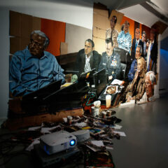 The Assassination Lesson // Acrylic on Cardboard, Video projector, DVD Player, Amplifier, Speakers, Postcards, Pizza box pallets, paint Brushes, Coffee Cups, Paint Tins, Digital Prints, Electrical Cable // 10 x 16 ft. // 2011