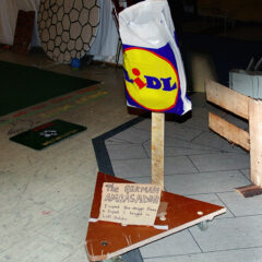 The German Ambassador minus the box of Ferro Roche which some hunger bastard robbed before I documented it // Wood, Wheels, Screws, Cardboard, Permanent Marker, Lidl Carrier Bag, Missing Ferro Roche // 50 x 40 x 120 cm // 2006