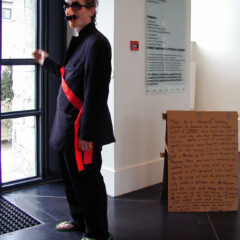 Shaky Hands: Wankers-Cramp Art-Elbow Challenge // Suit, Flip-Flops, Grocho Marx Glasses, Karl Marx Work Sash, Cigar, Card Board, Permanent Marker & Phantom Handshakes // Performance for the Duration of Opening Hours // 2005