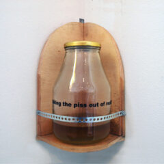 Putting the Piss in Art // Wood, Vinyl, Glass Jar, Metal Bracket, Text, Urine // 35 x 25 x 25 cm // 2005