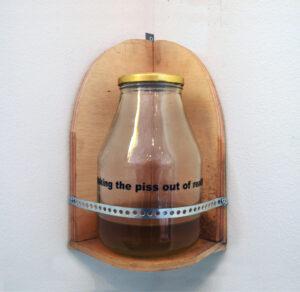 Putting the Piss in Art // Wood, Vinyl, Glass Jar, Metal Bracket, Text, Urine // 35 x 25 x 25 cm // 2005